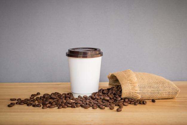 Tasse à café en papier blanc avec grains de café sur un bureau en bois