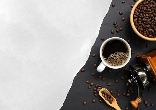 Tasse de café, papier blanc et haricot sur fond de table en bois noir. vue de dessus