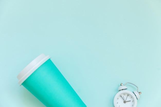 Tasse à café en papier bleu simplement à plat et réveil isolé sur fond bleu pastel