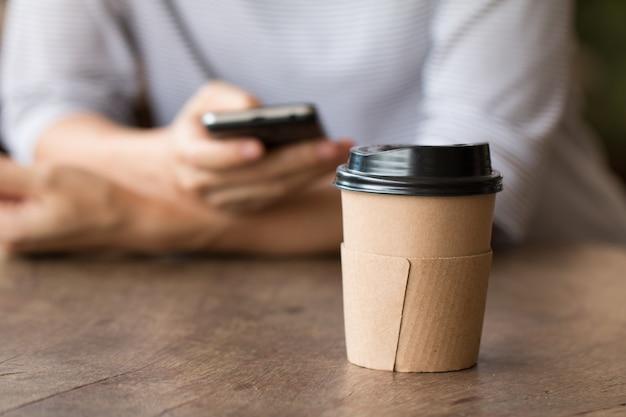 Tasse de café en papier boisson chaude sur un bureau en bois avec une femme travaillant sur téléphone intelligent