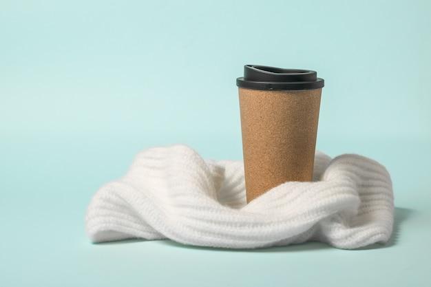 Tasse à café en papier brun enveloppé dans une écharpe sur un bleu