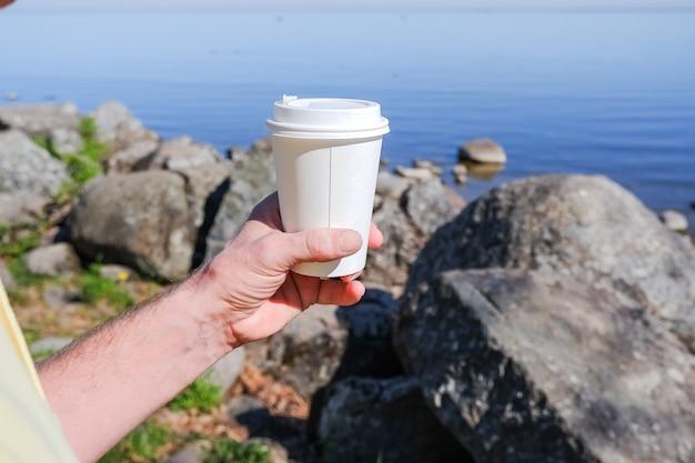 Tasse de café en papier du matin avec du café chaud savoureux à la main à l'extérieur sur la digue.la main tient une tasse en papier blanc pour les boissons à emporter, contre le magnifique mur de la mer, l'environnement