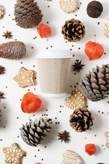 Tasse à café en papier à emporter entre biscuits, pommes de pin et autres décorations de noël. vue de dessus