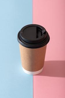 Tasse à café en papier sur fond rose pastel