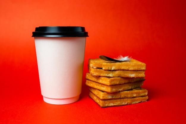Tasse à café en papier avec des gaufres et un stylo lumineux sur le rouge.