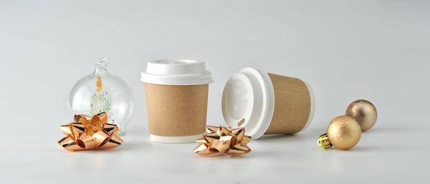Tasse à café en papier et grains de café sur fond blanc.