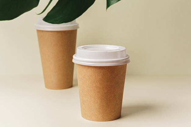 Tasse à café en papier jetable et feuille verte. concept d'écologie