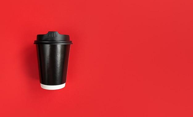 Tasse à café en papier noir pour aller sur fond rouge avec espace de copie.
