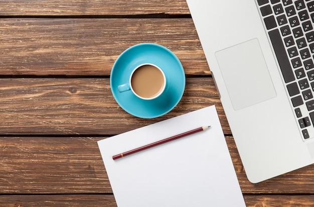 Tasse de café et papier avec ordinateur portable