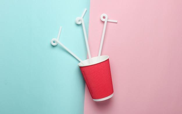 Tasse à café en papier avec pailles à cocktail, vue de dessus.