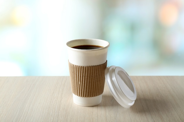 Tasse de café en papier sur la table sur une surface lumineuse