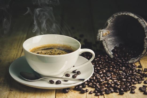 Tasse à café de parfum avec des grains rôtis sur fond en bois.