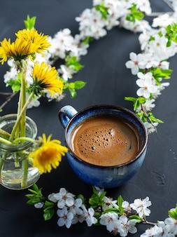 Une tasse de café parfumé, fleurs de cerisier, pissenlits jaunes en fleurs