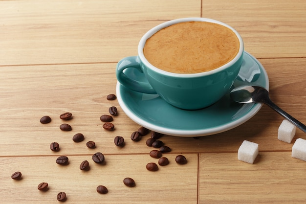 Une tasse de café parfumé en mousse sur une table en bois.
