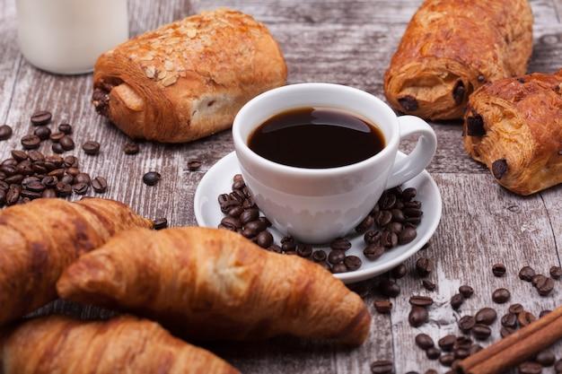 Tasse de café avec pâtisserie sur fond de table en bois rustique. fraîchement cuit.