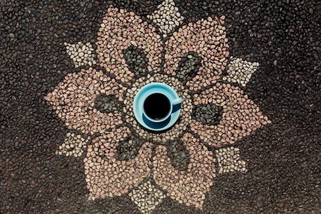 Tasse de café sur le pavage de fleurs de style balinais.