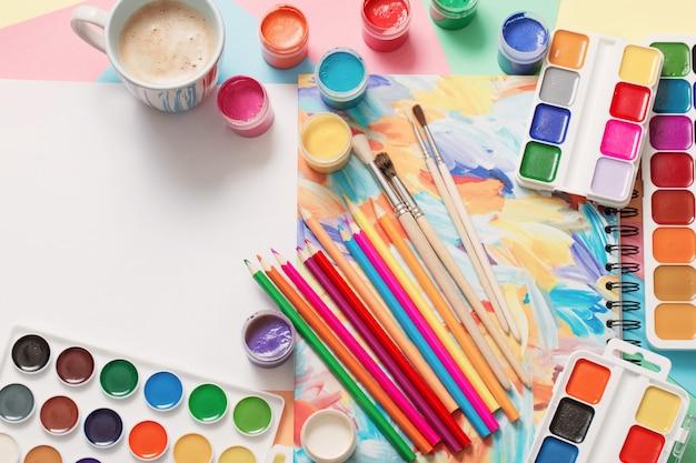 Tasse de café et peintures, crayons sur blanc