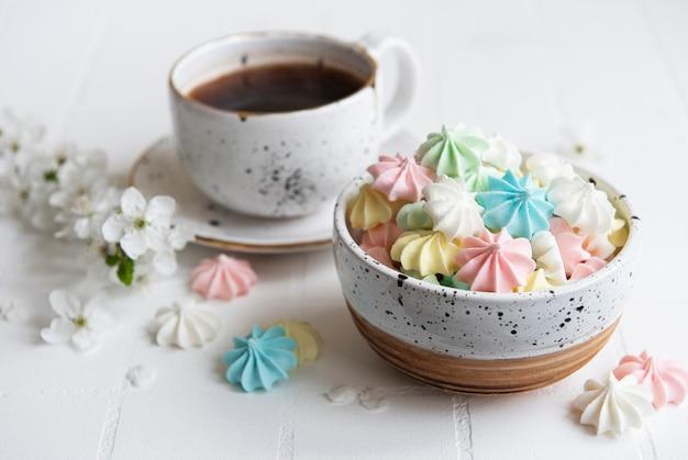 Tasse avec café et petites meringues dans le bol sur une surface carrelée