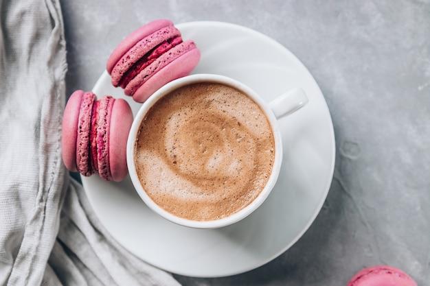 Tasse de café et petits gâteaux macarons sur une surface de béton gris
