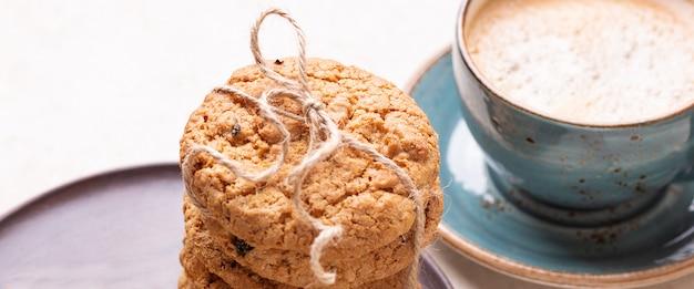 Tasse de café, pile de biscuits à l'avoine sur fond en bois blanc boulangerie maison bannière de gorisontal