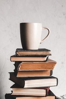 Une tasse de café sur une pile de livres sur fond gris