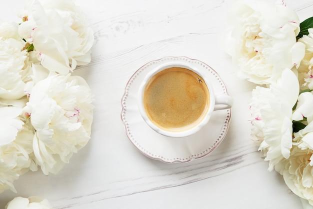 Une tasse de café et de pivoines blanches sur un fond en bois blanc.