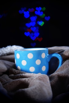 Tasse de café avec plaid sur une surface sombre