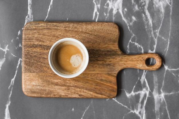 Tasse de café sur planche à découper sur fond de marbre gris