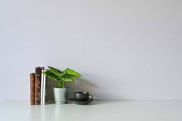 Tasse à café, des plantes et des livres sur l'espace de travail avec espace de copie de bureau.