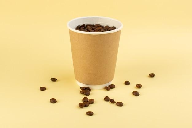 Une tasse de café en plastique vue de face avec des graines de café brun sur le mur jaune