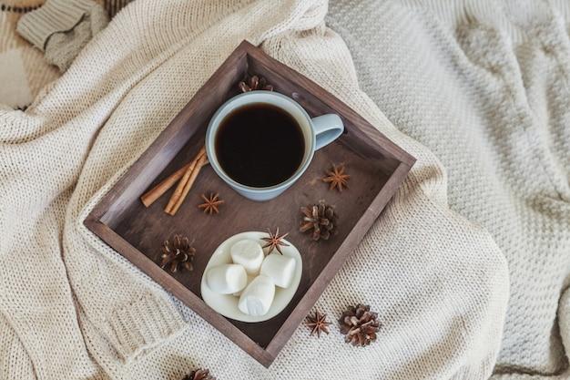 Tasse de café sur un plateau en bois rustique avec guimauve douce et pull en laine chaud