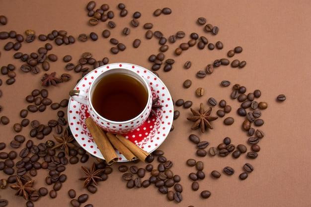 Tasse à café à pois noir épicé et grains de café en désordre sur fond marron