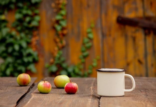 Tasse de café et pommes sur table en bois dans un jardin