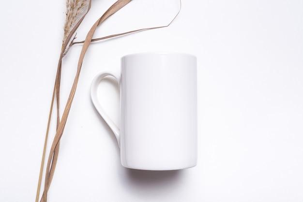 Tasse à café en porcelaine blanche décorée d'herbe séchée