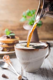 Tasse de café pour le petit déjeuner avec des crêpes.
