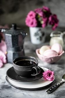 Tasse de café pour le petit déjeuner avec des guimauves sous forme de gâteaux de macaron dans un bol noir sur une table sombre et avec des fleurs dans un verre