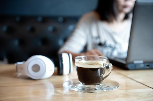 Tasse à café à la réception avec des personnes utilisant un ordinateur portable.
