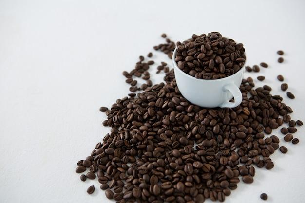 Tasse de café remplie de grains de café torréfiés