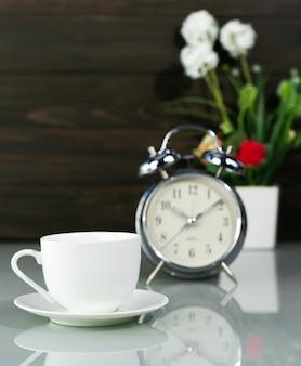 Tasse à café et réveil sur table