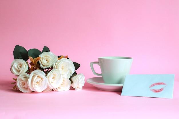 Tasse de café à la rose et baiser sur une enveloppe blanche isolée sur fond rose
