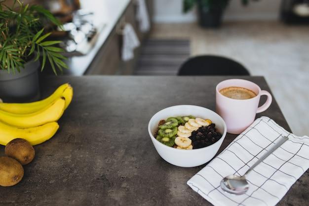 Tasse à café rose, bol avec kiwi et banane de fruits tropicaux hachés, myrtilles, cuillère sur comptoir de bar dans une cuisine loft élégante.