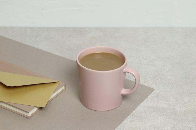 Tasse de café rose, enveloppe d'artisanat, des notes sur la texture de granit