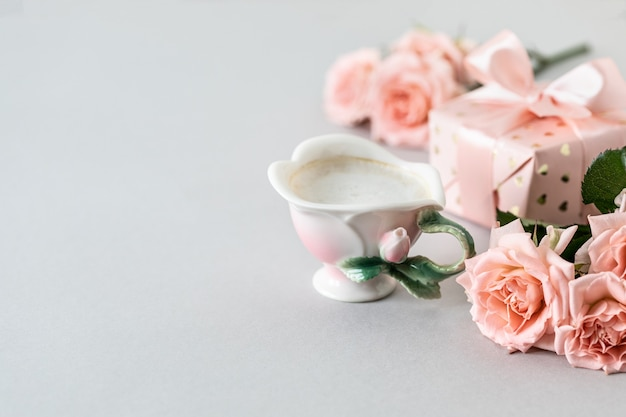 Tasse de café, roses roses, boîte avec un cadeau et roses roses sur une surface grise