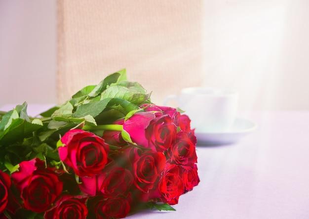 Une tasse de café et de roses rouges sur fond blanc