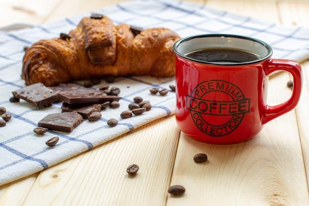 Tasse à café rouge et croissant sur fond en bois. la vue depuis le sommet. grains de café et chocolat