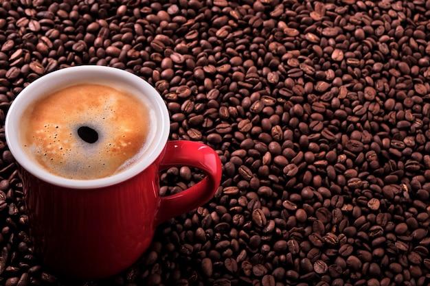 Tasse à café rouge avec espace de copie de fond haricots grillés