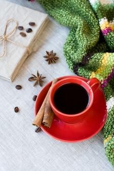 Tasse de café rouge avec des grains de café et des épices cannelle et anis étoile