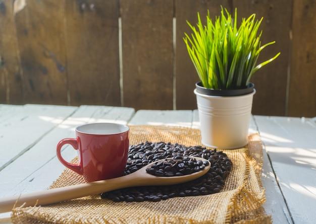 Tasse à café rouge et grains de café sur table blanche en bois.