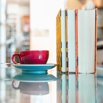 Tasse à café rouge et livre sur verre réfléchissant