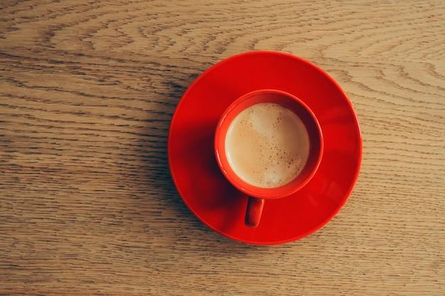 Tasse de café rouge sur une table en bois. vue de dessus